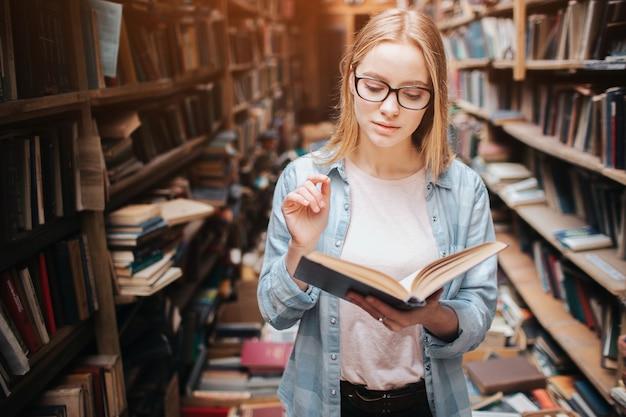 Jonge tiener is in de openbare bibliotheek. ze heeft een boek gevonden en gelezen. dit meisje is kalm, vredig en attent.
