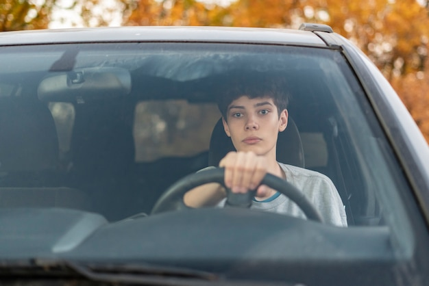 Jonge tiener leert hoe hij de auto moet besturen f