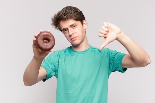 Jonge tiener man boze uitdrukking en een donut vasthouden?