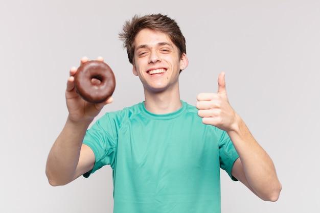 Jonge tiener man gelukkige uitdrukking en met een donut