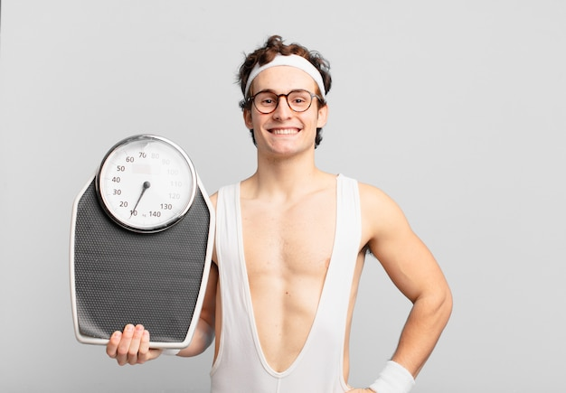 Jonge tiener man jonge gekke atleet gelukkige uitdrukking en met een weegschaal