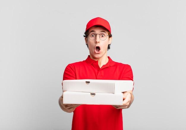 Jonge tiener man jonge pizza bezorgt man verraste uitdrukking
