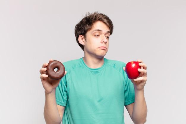 Jonge tiener man twijfelende of onzekere uitdrukking. dieet concept