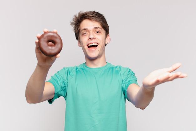 Jonge tiener man verraste uitdrukking en houdt een donut vast