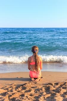 Jonge tiener meisje, zittend op het strand op zoek naar de zee