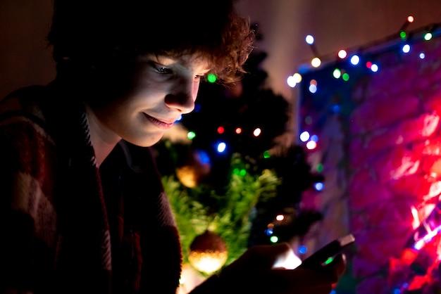 Jonge tiener met behulp van de smartphone op de kerstnacht thuis in de buurt van de boom.