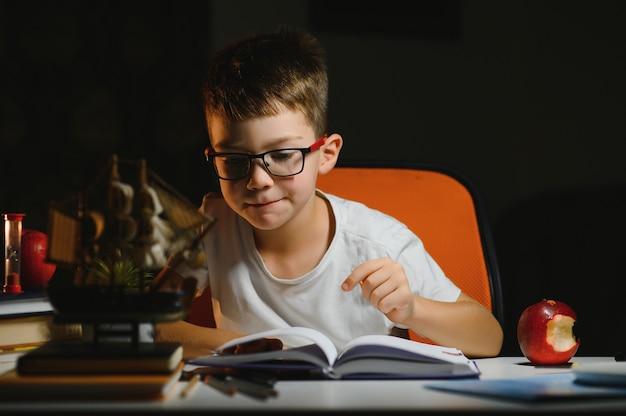 Jonge tiener schooljongen aan tafel huiswerk in de donkere kamer