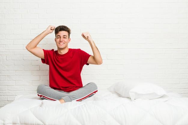 Jonge tiener student man bed viert een speciale dag, springt en hef armen met energie.