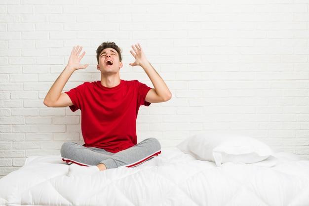 Jonge tiener student man op het bed schreeuwen naar de hemel, op zoek, gefrustreerd.