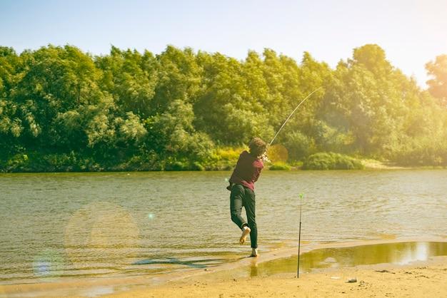 Jonge tiener visser in casual vis vangen op de rivieroever met rod op een zomerdag