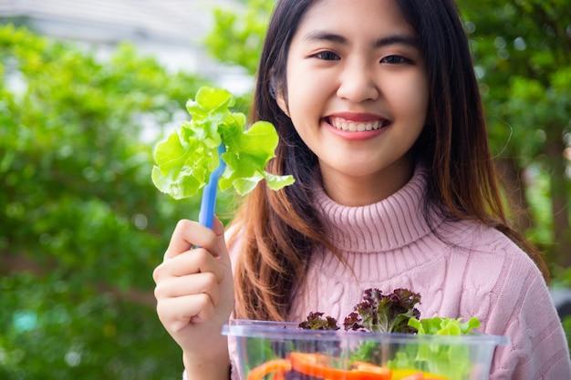 Jonge tiener vrouw met salade groente