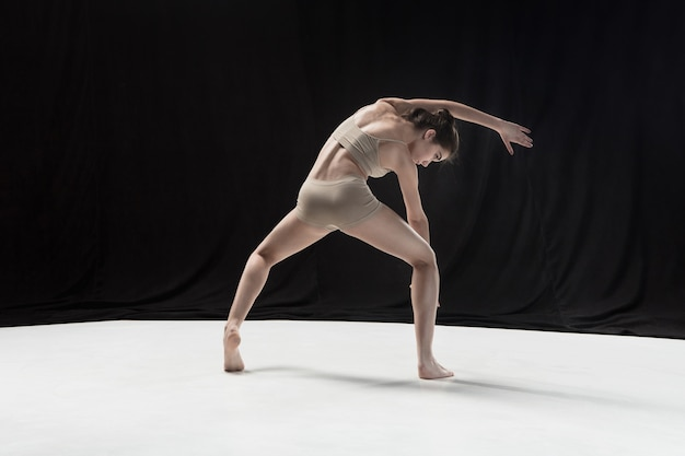 Jonge tienerdanser die op de witte achtergrond van de vloerstudio danst. ballerina project. choreografie en hedendaags concept
