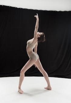 Jonge tienerdanser die op de witte achtergrond van de vloerstudio danst. ballerina project.