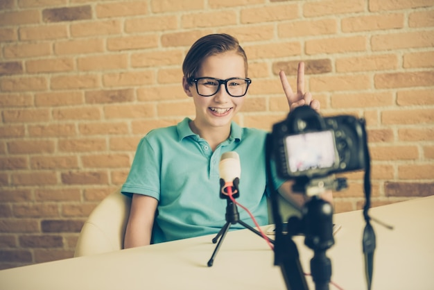 Jonge tienerjongen blogger camera instellen voor het opnemen van live vlog video-tutorialsessie thuis. it-bloggen of vloggen, hobby-uitzendingen op sociale media of online leercursusconcept