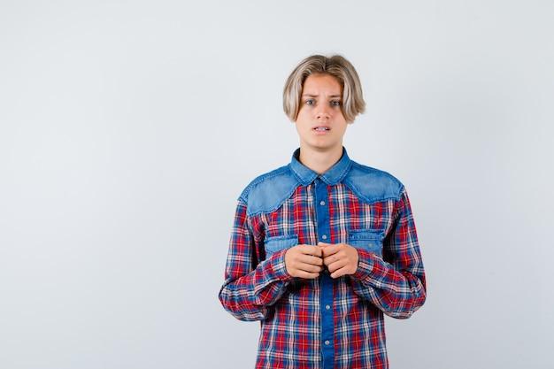 Jonge tienerjongen die camera in gecontroleerd overhemd bekijkt en verontrust kijkt. vooraanzicht.