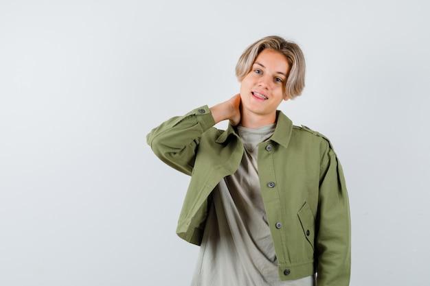 Jonge tienerjongen die de hand achter de nek houdt in t-shirt, jas en er joviaal uitziet, vooraanzicht.