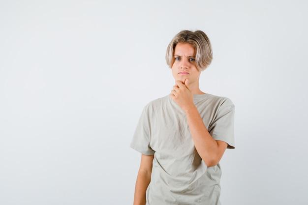 Jonge tienerjongen die de hand op de kin houdt in een t-shirt en er boos uitziet, vooraanzicht.
