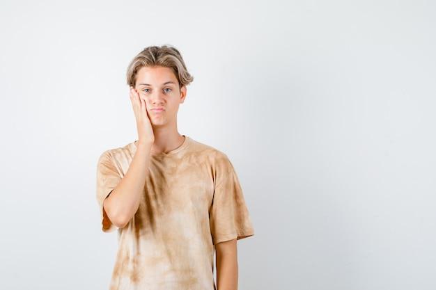 Jonge tienerjongen die de hand op de wang houdt in een t-shirt en er wanhopig uitziet. vooraanzicht.