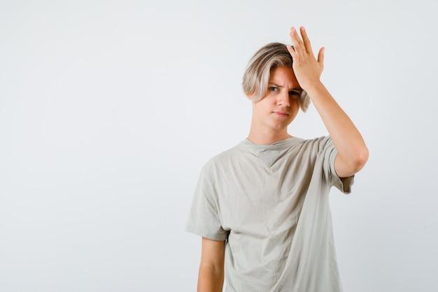 Jonge tienerjongen die de hand op het hoofd houdt in een t-shirt en er vergeetachtig uitziet. vooraanzicht.