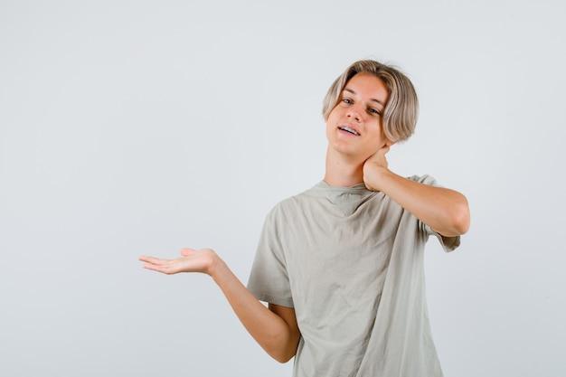 Jonge tienerjongen die de palm opzij spreidt, de hand op de nek houdt in een t-shirt en er vrolijk uitziet. vooraanzicht.