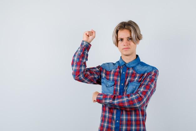 Jonge tienerjongen die de spieren van de arm in een geruit overhemd toont en er zelfverzekerd uitziet, vooraanzicht.