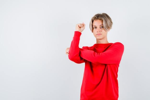 Jonge tienerjongen die de spieren van de arm in een rode trui toont en er trots uitziet. vooraanzicht.