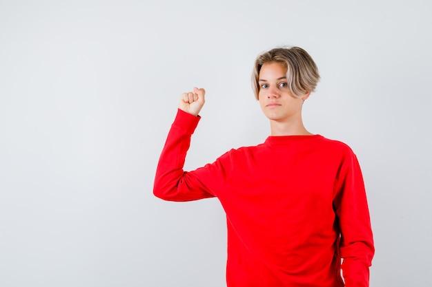 Jonge tienerjongen die de spieren van de arm in een rode trui toont en er zelfverzekerd uitziet. vooraanzicht.