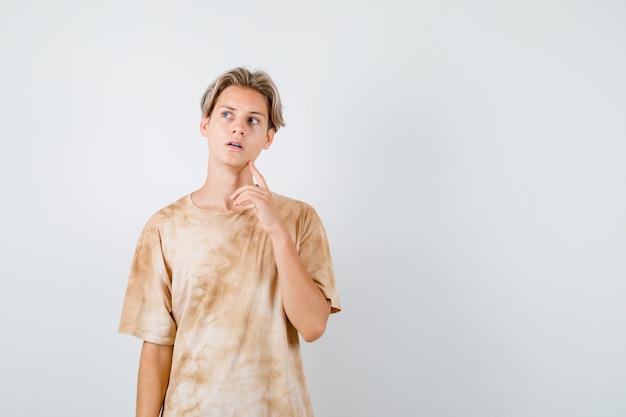 Jonge tienerjongen die de vinger op de kaak houdt, omhoog kijkt in t-shirt en peinzend kijkt, vooraanzicht.