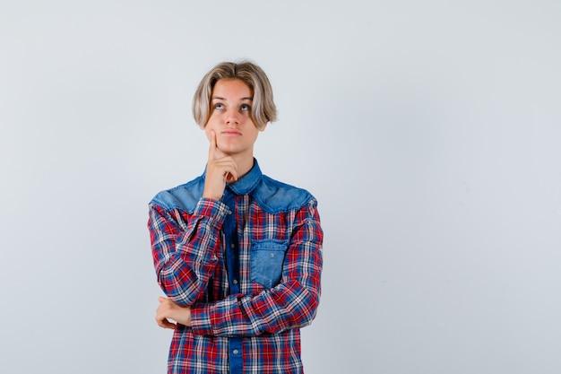 Jonge tienerjongen die de vinger op de wang houdt, omhoog kijkt in een geruit overhemd en peinzend kijkt. vooraanzicht.