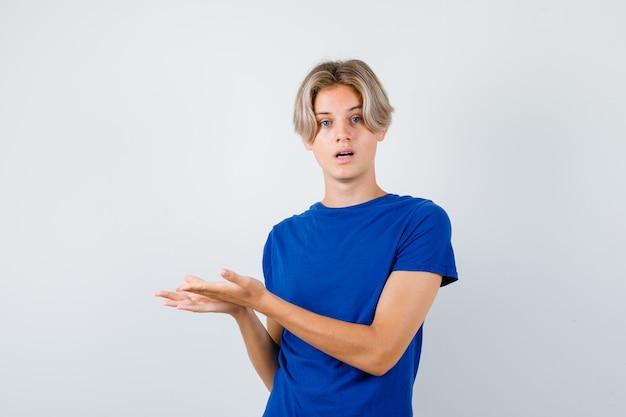 Jonge tienerjongen die doet alsof hij iets in een blauw t-shirt laat zien en er verbaasd uitziet. vooraanzicht.