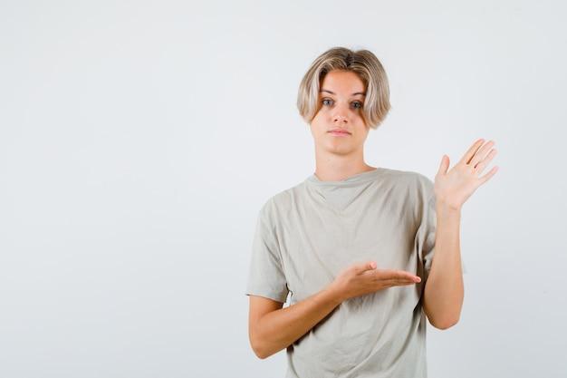 Jonge tienerjongen die doet alsof hij iets in een t-shirt laat zien en er verbaasd uitziet. vooraanzicht.