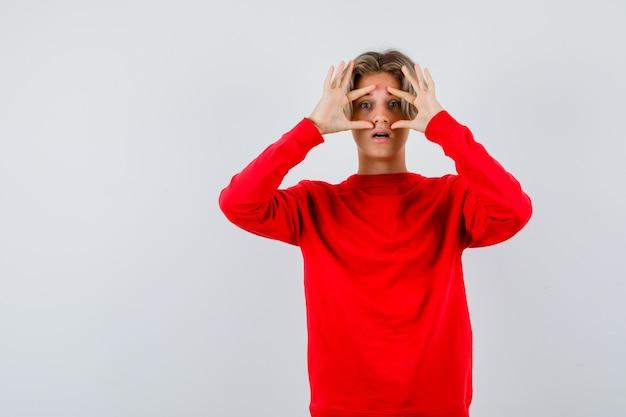 Jonge tienerjongen die door vingers in rode trui gluurt en zich afvroeg, vooraanzicht.