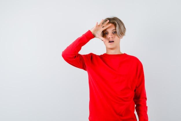 Jonge tienerjongen die door vingers in rode trui kijkt en zich afvraagt, vooraanzicht.