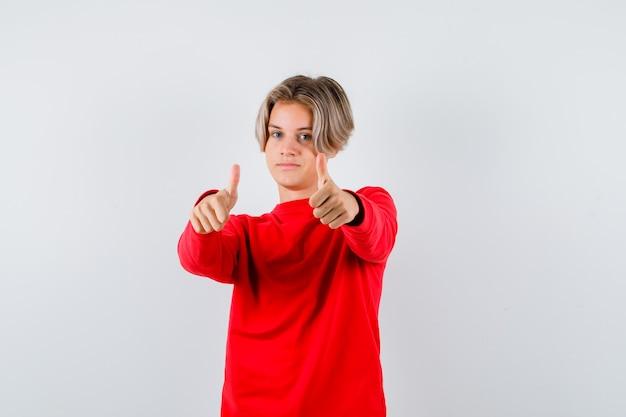 Jonge tienerjongen die dubbele duimen in rode trui toont en er tevreden uitziet, vooraanzicht.