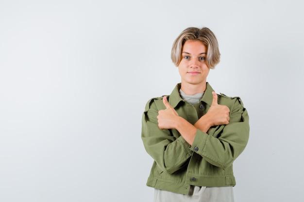 Jonge tienerjongen die dubbele duimen toont in t-shirt, jas en er zelfverzekerd uitziet, vooraanzicht.