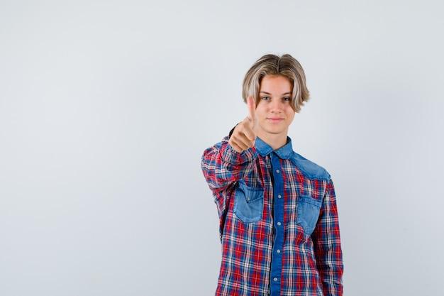 Jonge tienerjongen die duim in geruit overhemd toont en er trots uitziet, vooraanzicht.