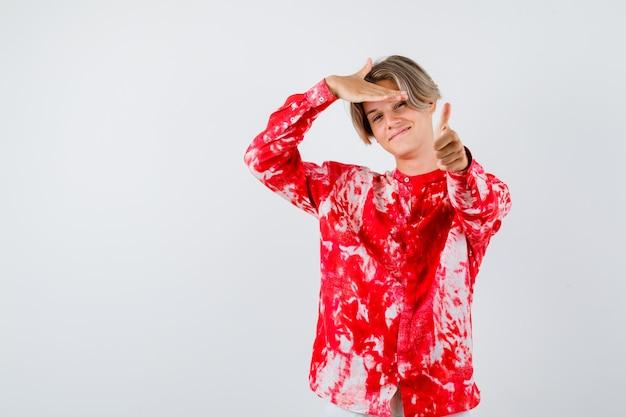 Jonge tienerjongen die duim toont, hand boven het hoofd in overhemd houdt en vrolijk kijkt, vooraanzicht.