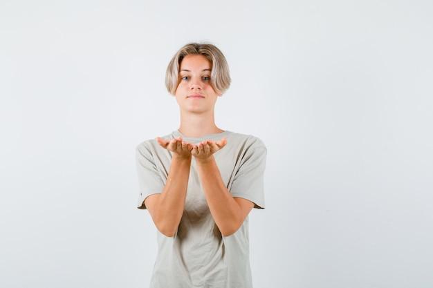Jonge tienerjongen die een gebaar maakt of ontvangt in een t-shirt en er vrolijk uitziet