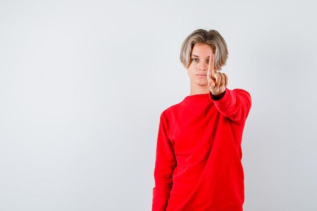 Jonge tienerjongen die een klein gebaar in rode trui laat zien en er serieus uitziet, vooraanzicht.