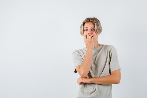 Jonge tienerjongen die emotioneel nagels bijt in t-shirt en er angstig uitziet. vooraanzicht.
