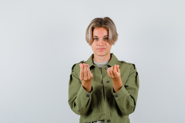 Jonge tienerjongen die geldgebaar maakt in een groen jasje en er verstandig uitziet. vooraanzicht.