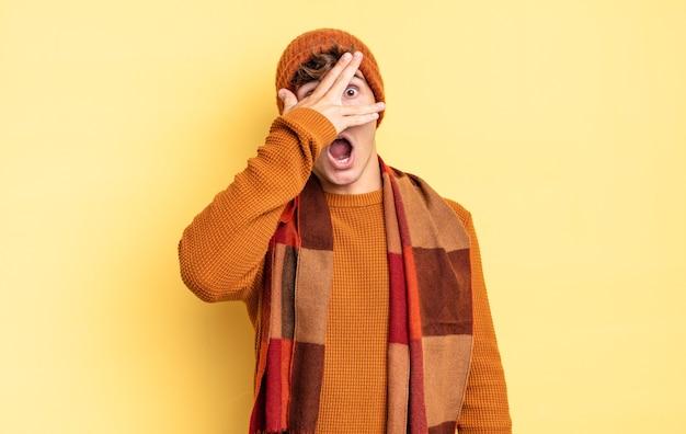 Jonge tienerjongen die geschokt, bang of doodsbang kijkt, zijn gezicht bedekt met de hand en tussen de vingers gluurt