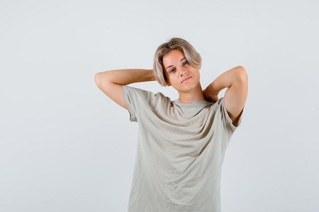 Jonge tienerjongen die hand achter hoofd houdt