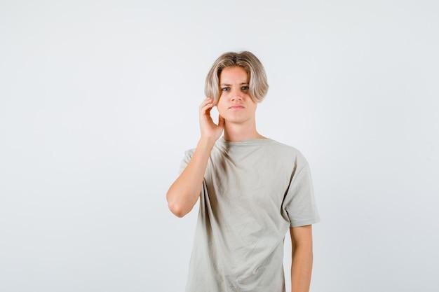 Jonge tienerjongen die hand in de buurt van oor in t-shirt houdt en verward kijkt, vooraanzicht.