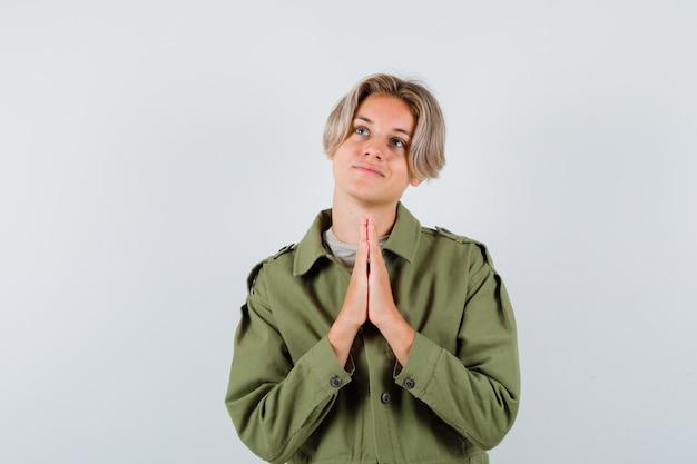 Jonge tienerjongen die handen in een biddend gebaar houdt, omhoog kijkt in een groen jasje en er dromerig uitziet, vooraanzicht.