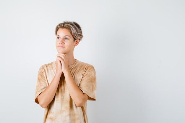 Jonge tienerjongen die handen onder de kin omklemt, wegkijkt in t-shirt en er dromerig uitziet, vooraanzicht.