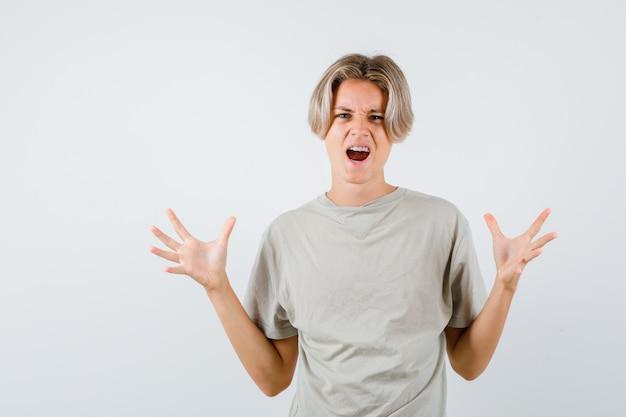 Jonge tienerjongen die handen op een agressieve manier in t-shirt opsteekt en er geïrriteerd uitziet