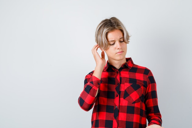 Jonge tienerjongen die hoofd krabt, neerkijkt in een geruit overhemd en peinzend kijkt, vooraanzicht.