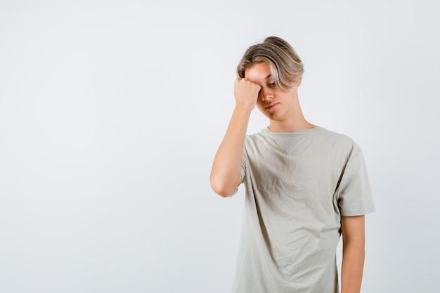 Jonge tienerjongen die hoofdpijn in t-shirt voelt en overstuur kijkt. vooraanzicht.