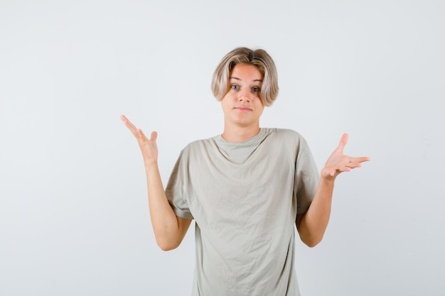 Jonge tienerjongen die hulpeloos gebaar in t-shirt toont en verbaasd kijkt. vooraanzicht.